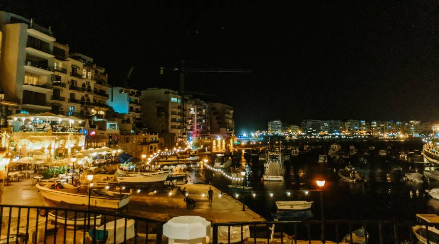 St Julian's Harbour in Malta lit up at night time
