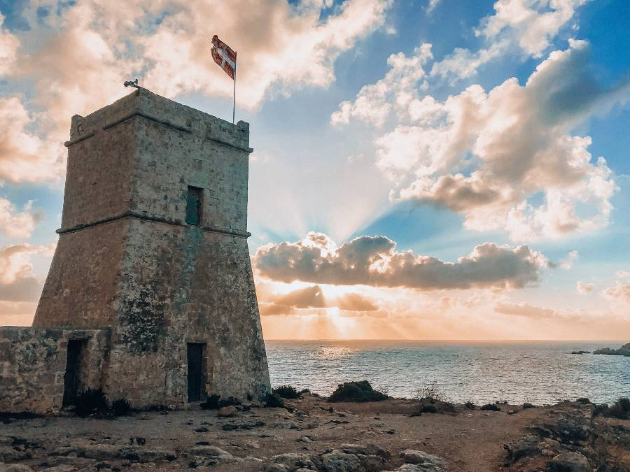 The sunsetting behind the watch tower of Golden Bay in Malta