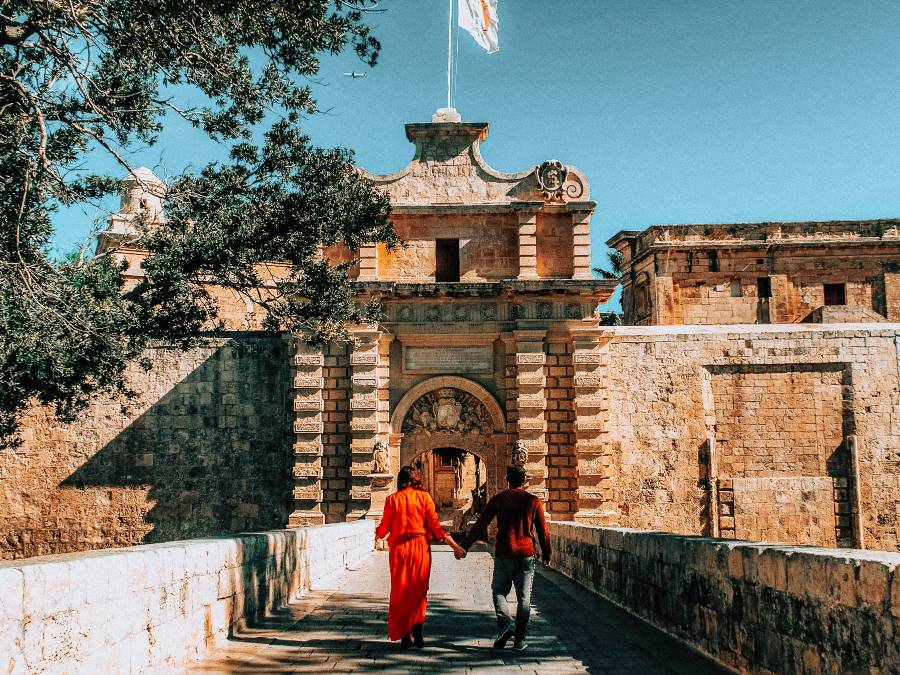 A couple walking to an old stone building in the silent city in Malta